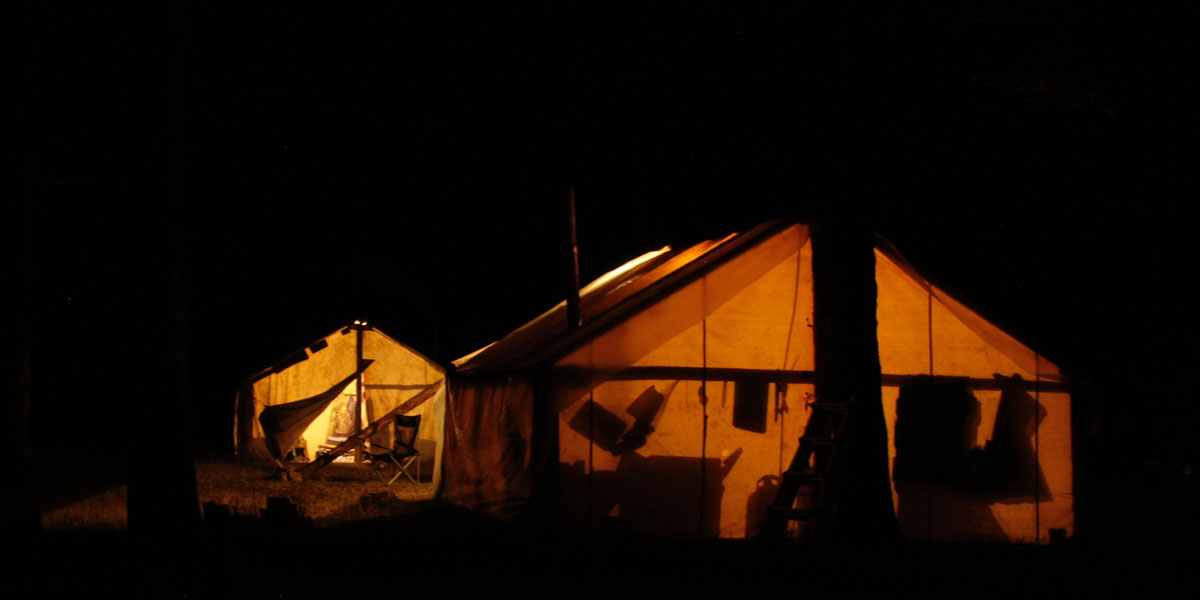canvas wall tents at night with silhouettes