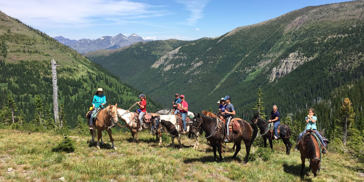 horses and riders resting atop mountain